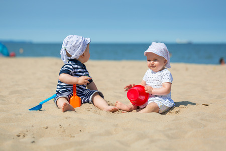 Baby twins playing at the beach of Baltic Sea, Poland