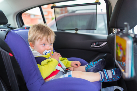 child safety: Baby boy in a car on child safety seat watching cartoon on the tablet Stock Photo