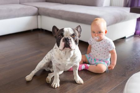 Meisje zitten met Franse bulldog op de vloer