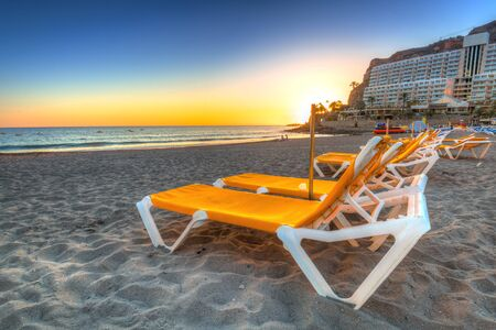Deckchairs on the beach of Taurito at sunset, Gran Canaria Stock Photo