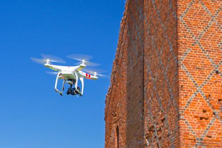 phantom: GRUDZIADZ, POLAND - AUGUST 27 ,2015: Flying drone quadcopter Dji Phantom 2 with digital camera GoPro HERO4 filming ruins of the castle.