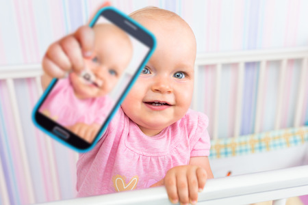 Baby girl taking selfie with a cell phone camera