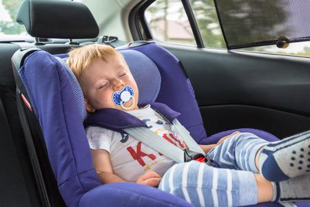 小さな男の子は車の安全座席に寝ています。