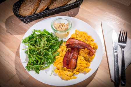 Breakfast table with crambled eggs, bacon and ruccola salad on the plate Stock Photo