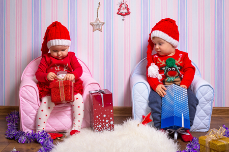 Boy and girl twins posing with Christmas presents Stock Photo