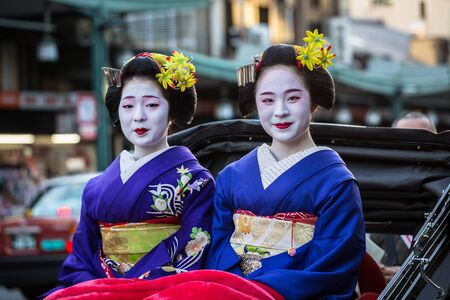 consist: KYOTO, JAPAN - NOVEMBER 11, 2016: Maiko women, apprentice geisha on the street of Kyoto, Japan. Their jobs consist of performing songs, dances, and playing the shamisen