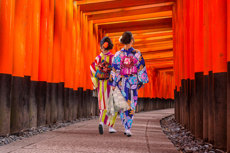 Women in traditional japanese kimonos walking at Fushimi Inari Shrine in Kyoto, Japan Stock Photo
