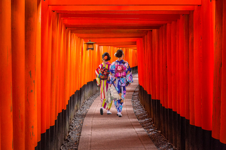 Women in traditional japanese kimonos walking at Fushimi Inari Shrine in Kyoto, Japan 写真素材