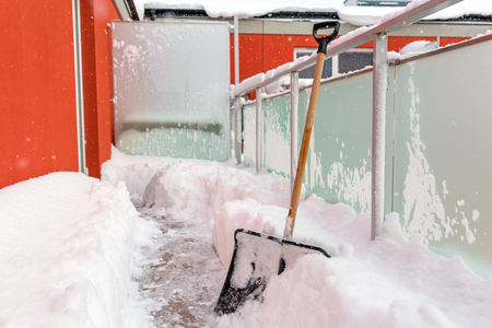 Snow shovel on the balcony after winter snowfall