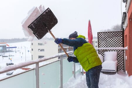 shoveling: Man shoveling the show on the terrace after heavy snowfall
