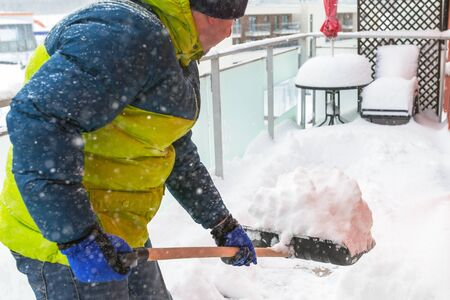 Man shoveling the show on the terrace after heavy snowfall