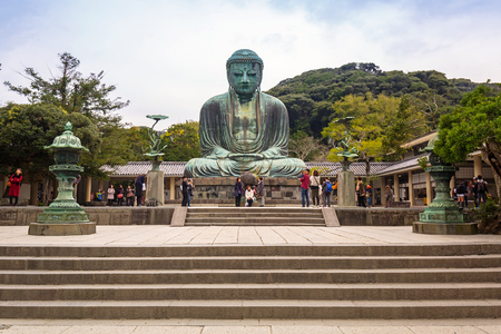 KAMAKURA, JAPAN - NOVEMBER 8, 2016: Tourists at statue of The Great Buddha of Kamakura, Japan. Monumental outdoor bronze statue of Amida Buddha is one of the most famous icons in Japan. Editorial