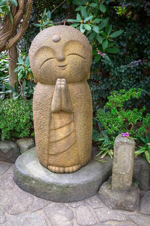 Smiling stone buddha monk statue at Hasedera temple in Kamakura, Japan Stock Photo - 75154753