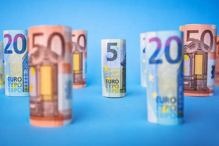 Rolled up euro banknotes on blue background Stock Photo