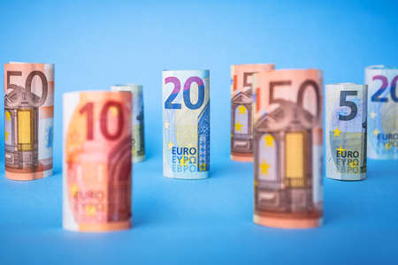 Rolled up euro banknotes on blue background Stock Photo - 75164566