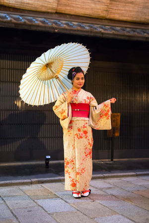 KYOTO, JAPAN - NOVEMBER 10, 2016: Young woman wearing traditional japanese kimono walk on the street of Gion, Kyoto old town, Japan. Kimono is a Japanese traditional garment.