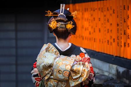 KYOTO, JAPAN - NOVEMBER 11, 2016: Woman wearing traditional japanese kimono walk on the street of Gion, Kyoto old town, Japan. Kimono is a Japanese traditional garment. 에디토리얼