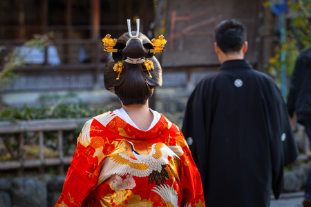 KYOTO, JAPAN - NOVEMBER 11, 2016: Woman wearing traditional japanese kimono walk on the street of Gion, Kyoto old town, Japan. Kimono is a Japanese traditional garment. Editorial