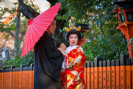 KYOTO, JAPAN - NOVEMBER 11, 2016: Japanese couple wearing traditional japanese kimonos walk on the street of Gion, Kyoto old town, Japan. Kimono is a Japanese traditional garment.