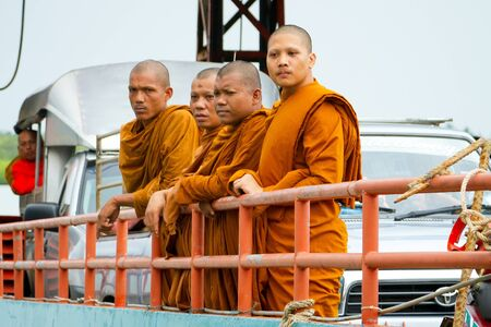 BANG MUANG, THAILAND - NOVEMBER 5, 2012: Thai monks in orange robes travelling on the ferry to the Koh Kho Khao island in Thailand. Orange color for clothes is traditional for thai buddists.