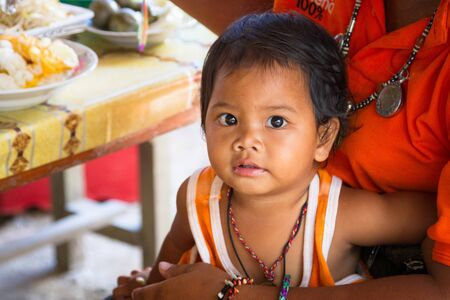 koh kho khao: KHAO LAK, THAILAND - NOVEMBER 5, 2012: Cute toddler portrait sitting on mother knees in Khao Lak, Thailand. Many people in Thailand working with little babies with them.