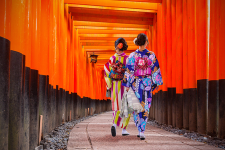 Women in traditional japanese kimonos walking at Fushimi Inari Shrine in Kyoto, Japan Standard-Bild