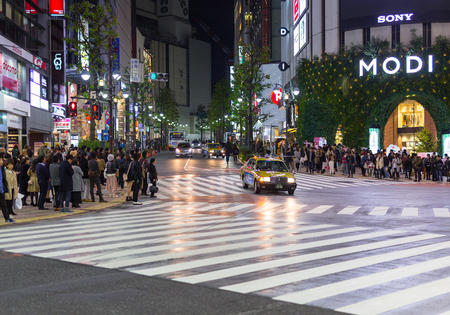 TOKYO, JAPAN - NOVEMBER 12, 2016: Busy streets of Shibuya district in Tokyo at night, Japan. Shibuya is the shopping district which surrounds Shibuya Station, one of Tokyos busiest railway stations.