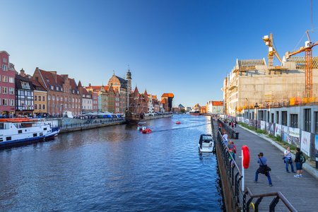GDANSK, POLAND - AUGUST 14, 2017: Tourists st the port crane in old town of Gdansk. Port crane in Gdansk built between 1442 and 1444 is the city symbol and the oldest surviving port crane in Europe.