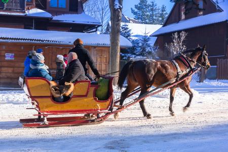 ZAKOPANE, POLEN - DECEMBER 30, 2016: Niet geïdentificeerde mensen op de paardkar in sneeuwzakopane-stad, Polen. Paard en wagen rijden is een toeristische attractie in Zakopane.