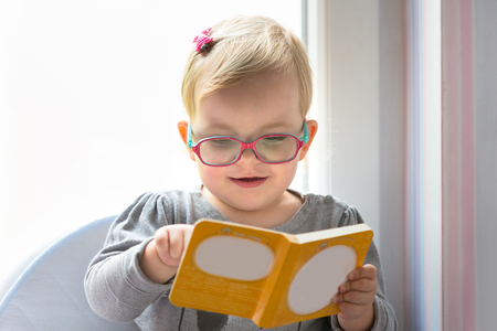 Little girl reading book at home