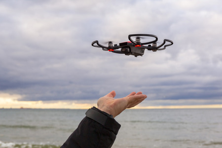 Drone landing on hand at Baltic Sea in Poland