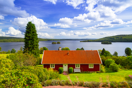 Traditional red cottage house at the lake in Sweden Foto de archivo