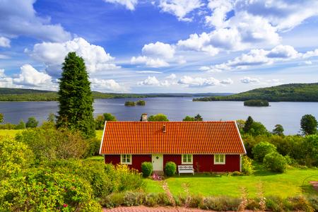 Tradycyjny czerwony domek nad jeziorem w Szwecji