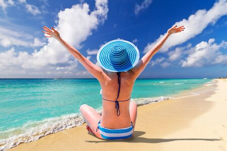 Beautiful woman in blue hat on the tropical beach Stock Photo