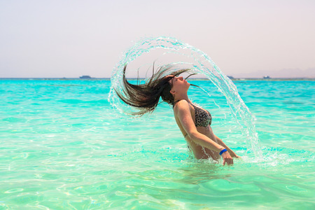 Young woman jumping out of turquoise sea water Stock Photo
