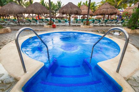PLAYA DEL CARMEN, MEXICO - JULY 12, 2011: Luxury swimming pool scenery at RIU Yucatan Hotel in Playa del Carmen, Mexico. RIU Hotels & Resorts has more than 100 hotels in 19 countries.