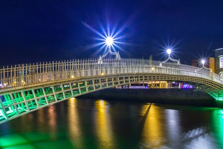 DUBLIN, IRELAND - FEBRUARY 20, 2012: The hapenny bridge in Dublin at night, Ireland. Dublin is the capital and largest city of Ireland. Located on the east coast, at the mouth of the River Liffey.