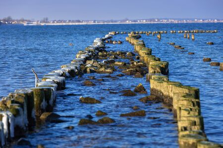 Frozen wooden breakwaters line at Baltic Sea, Babie Doly, Poland Stock Photo