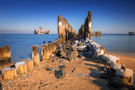Frozen wooden breakwaters line at Baltic Sea in Poland