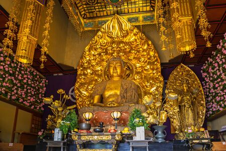 Kamakura, Japan - November 10, 2016: Gold buddha statue of Hase-dera temple in Kamakura, Japan. Hase-dera Buddhist temple is famous for housing a massive wooden statue of Kannon Standard-Bild - 99672332