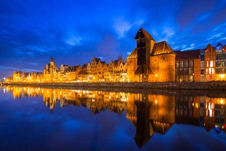 Historic port crane in Gdansk reflected in Motlawa river at dusk, Poland