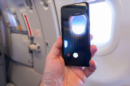 Making photos during the flight by a phone camera Stock Photo