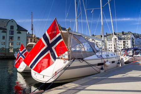 Yacht with the flag of Norway in Alesund town marina. Stock Photo