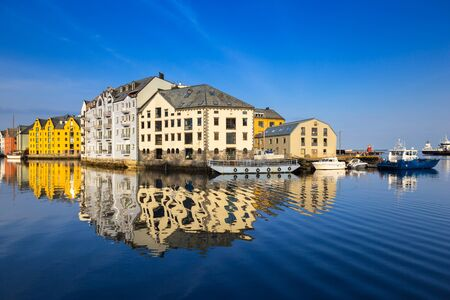 Architecture of Alesund town reflected in the marina canal, Norway