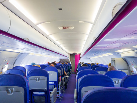 Interior of passenger airplane with people on seats Stock Photo