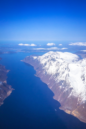 Aerial view of snowy Norway coastline from the plane