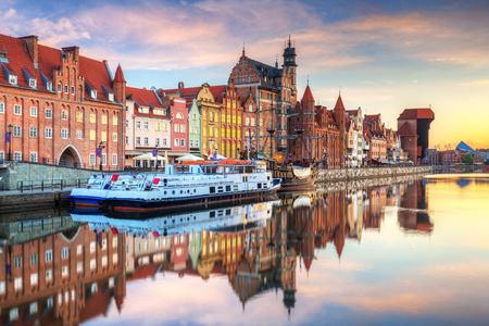 Beautiful old town of Gdansk reflected in Motlawa river at sunrise, Poland. Редакционное