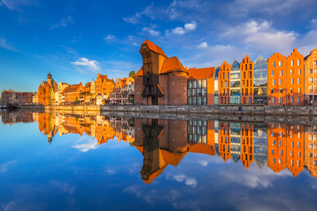 Historic port crane of Gdansk reflected in Motlawa river at sunrise, Poland