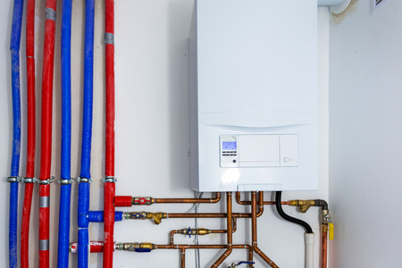 Pipes and boiler of gas heating system in the house Stock Photo