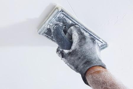 Hand of plasterer polishing ceiling Stock Photo